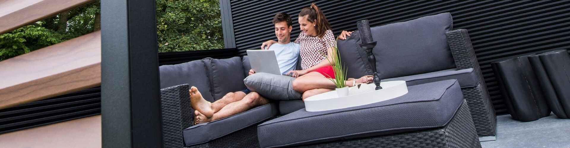 Couple with laptop sitting on outdoor furniture